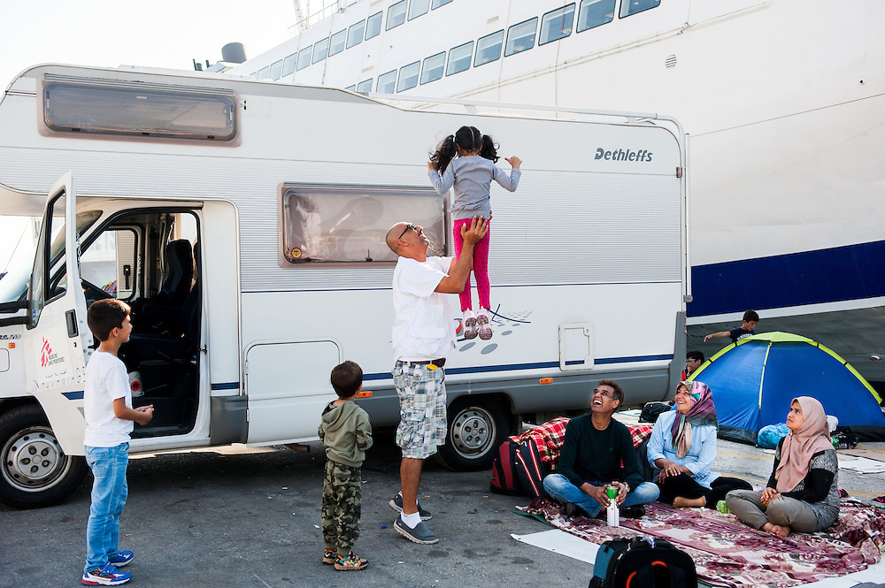 The MSF Arabic translator Ihnab Abassi plays with Aghan children at the port of Mytiline.