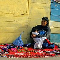 North America, Mexico, Baja California, Ensenada.  A woman and her baby await tourists to buy handmade trinkets.