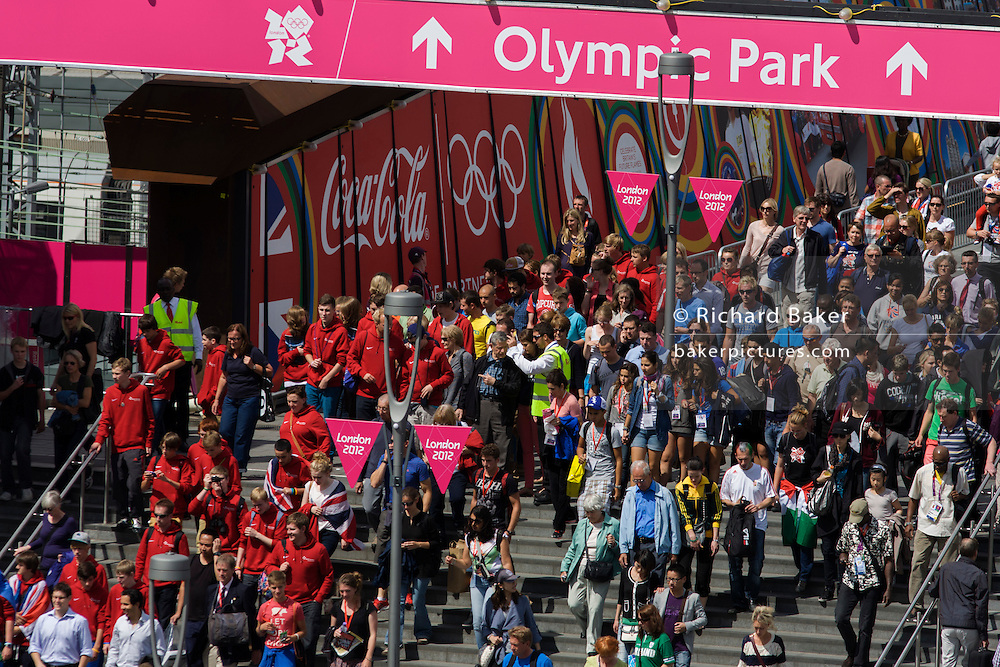 Aerial view of spectator crowds at the Westfield City shopping complex, Stratford that leads to the Olympic Park during the London 2012 Olympics, the 30th Olympiad. Large Coca-Cola ads line the walkway to the Olympic Park. Situated on the fringe of the 2012 Olympic park, Westfield is Europe's largest urban shopping centre. The £1.45bn complex houses more than 300 shops, 70 restaurants, a 14-screen cinema, three hotels, a bowling alley and the UK's largest casino. It provides the main access to the Olympic park with a central 'street' giving 75% of Olympic visitors access to the main stadium so retail space...