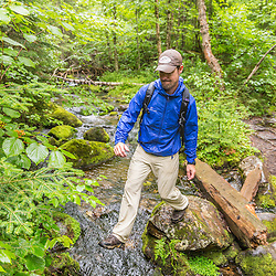 A man crosses Perham Stream on Lone Mountain and the Appalachian Trail in Mount Abram Township, Maine. High Peaks.
