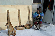 Khabarovsk, Russia, 01/03/2004.&#xD;A Chinese woman mends bags at a street market. Many Chinese cross the nearby border to sell cheap goods on the street.&#xD;<br />