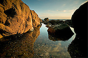Sunset over crystal clear rock pool in low cliffs near Rhosneigr, Anglesey, Wales