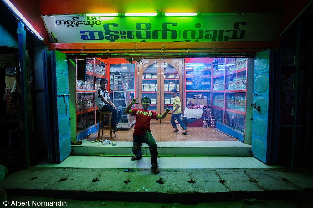 Excited boy in front of shop, Paper Elephant Festival, Kyaukse, Mandalay