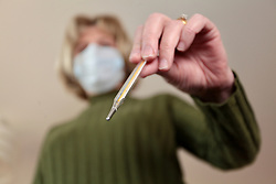 Covid 19 - Woman wearing a face mask with a thermometer, UK March 2020. Posed by model