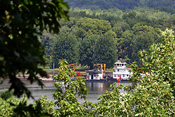 A U.S. Coast Guard tugboat heads downstream passing Starved Rock State Park on the Illinois River