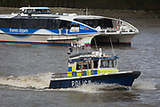 The Metropolitan Police Marine Policing Units Thames river police launch, John Harriott IV, passes a Thames Clipper passenger riverboat service on the Thames river, on 17th January 2020, in London, England. John Harriott 1745–1817 was an English seafarer, founder of the Marine Police Force.