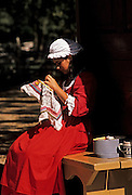 Image of a woman reenactor embroidering on Duke of Gloucester Street in Colonial Williamsburg, Virginia, east coast by Randy Wells