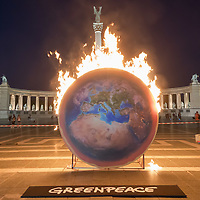 Greenpeace activist demonstrate the importance of climate catastrophe with an Earth replica set on fire on Hungary's Heroes square in Budapest, Hungary on Sept. 4, 2019. ATTILA VOLGYI