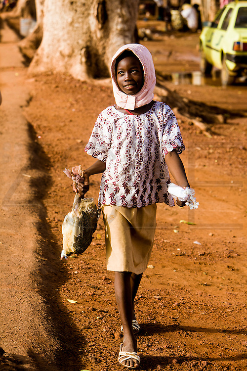 A girl carrying a chicken. At the confluence of the Niger and the Bani rivers, between Timbuktu and Ségou, Mopti is the second largest city in Mali, and the hub for commerce and tourism in this west-african landlocked country.