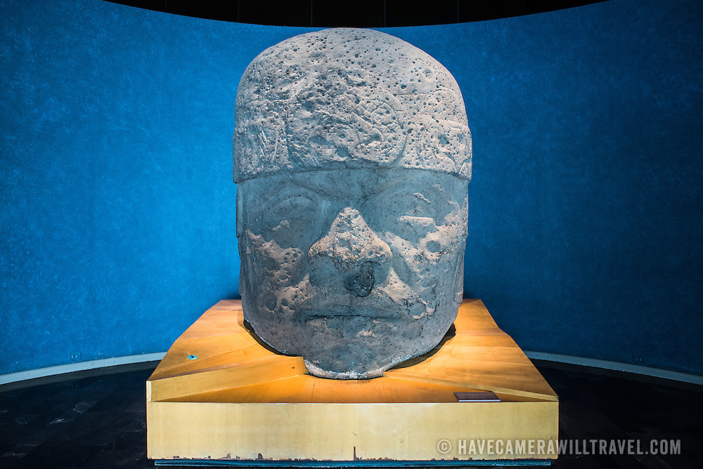 MEXICO CITY, MEXICO--A colossal head (or Cabeza Colosal) carved of basalt from the Olmec culture and dating to around 1200-600 BC. The National Museum of Anthropology showcases  significant archaeological and anthropological artifacts from the Mexico's pre-Columbian heritage, including its Aztec and indiginous cultures.