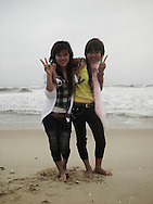 Two young vietnamese girls pose on the beach and make a V sign with their fingers. Quang Binh province, Viet nam, asia.