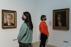 """© Licensed to London News Pictures. 15/10/2020. LONDON, UK.  London, UK. 15 October 2020. Staff members view (L to R) """"Self-Portrait"""", 1959, and """"Self-Portrait"""", 1914, both by Stanley Spencer. The works are part of new displays in Tate Britain's three collection routes: Rothko and Turner (a new route to celebrate 50 years since Mark Rothko first gave Tate his iconic Seagram Murals to join paintings he so admired by JMW Turner), British Art 1540-1920 and British Art 1930-Now.  Visitors may book online for free to visit the museum.  Photo credit: Stephen Chung/LNP"""