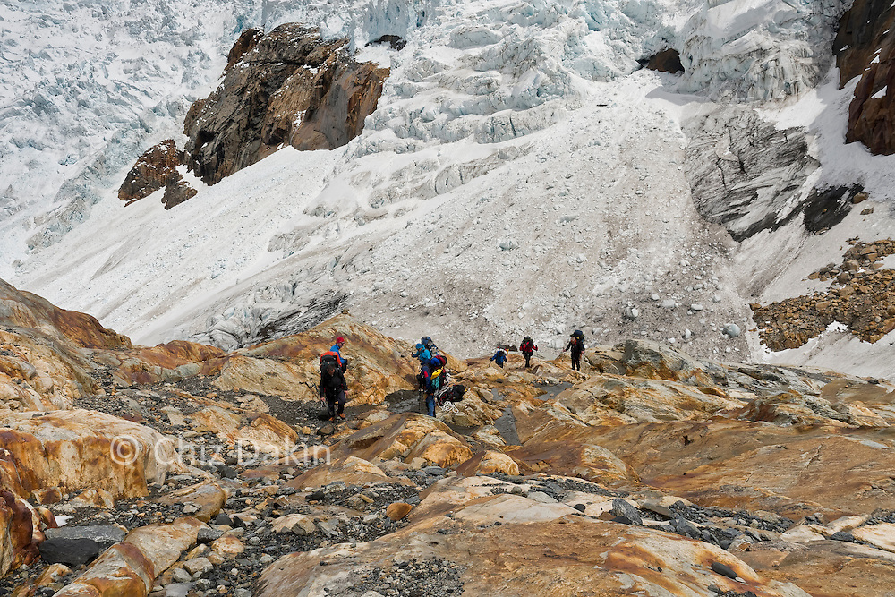Team heading up across a newly exposed rock section to the long snow plod onto the Ice Cap