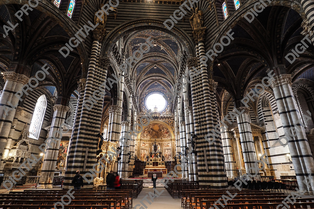 Main aisle and altar from the interior of the Siena Dome (Duomo) with few visitors during the day