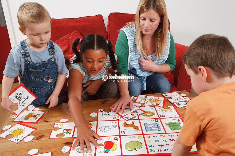 Nursery nurse doing a puzzle with children