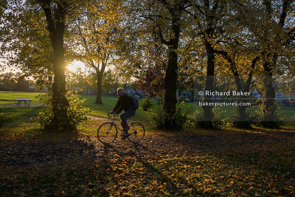 A cyclist pedals through an Autumnal park.