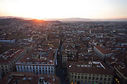 With an autumnal sun setting over the hills to the west of the city, we see in the foreground the streets, rooftops and housing of Florence, viewed from an aerial height from Giotto's Bell Tower (campanile). Florence (Firenze) is the capital city of the Italian region of Tuscany and of the province of Florence. It is the most populous city in Tuscany, with 367,569 inhabitants (1,500,000 in the metropolitan area). The city lies on the River Arno and is known for its history and its importance in the Middle Ages and in the Renaissance, especially for its art and architecture. A centre of medieval European trade and finance and one of the wealthiest cities of the time, Florence has been called the Athens of the Middle Ages.