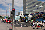 A Santander cyclist and young pedestrian cross the road opposite the soon to be demolished Shopping Centre (right) at Elephant & Castle, south London.