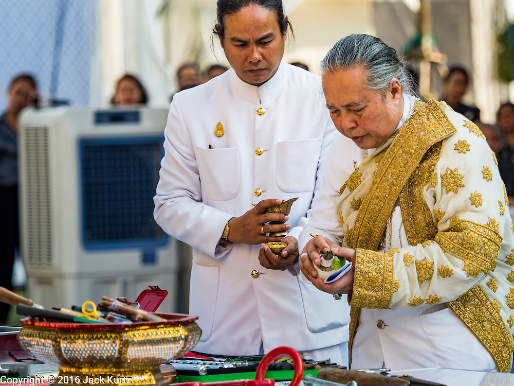 """19 DECEMBER 2016 - BANGKOK, THAILAND:  PHRA MAHA RAJA GURU BIDHI SRI VISUDHIGUN (right), head Brahmin in the Royal Ceremonial Affairs Division, leads a service during the """"Spirit Appeasing"""" Ceremony held for the Royal Chariots at the Bangkok National Museum. The chariots will be used to take the body of Bhumibol Adulyadej, the Late King of Thailand, and members of the Royal funeral cortege to the cremation site on Sanam Luang for His Majesty's cremation. This will be the first cremation of a Thai King since 1950, when King Bumibol's brother, Rama VIII, Ananda Mahidol, was cremated. The design of the royal crematorium is based on Buddhist cosmology, with the main peak of Mount Sumeru (also known as Meru in Hindu cosmology) at center and eight other peaks signifying the levels of the universe. The crematorium will be decorated with mythical creatures such as garuda, angels, and Himmapan Forest creatures. The structure and funeral pyre will stand just over 50 meters tall. The exact date of the King's cremation has not been set yet but is expected to be late next year.    PHOTO BY JACK KURTZ"""