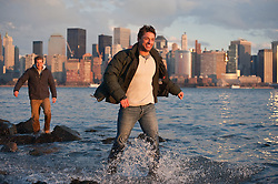 Two men walking along the shore of the Hudson River, with New York City in the background