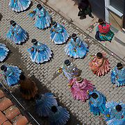 One of Bolivia's most famous festivals, The festival of the Virgen de la Candelaria takes place in the usually quite rural fishing village of Copacabana on the shores of Lake Titicaca. For three days from February 2nd to the 5th the village is transformed by the Aymara indigenous community who celebrate with street parades, colorful costumes, music, traditional bands, dancing and enormous amount of drinking and celebrating.<br /> Vehicles are blessed with beer and people gather for days to celebrate in a mixture of Catholic and native religions.<br /> The Virgen de la Candelaria is revered for a series of miracles, recounted in Nuestra Senora de Copacabana. Legend has it in 1576, some Inca fisherman were caught in a terrible storm on Lake Titicaca. As they prayed for help, the Virgin Mary appeared and led them to safety. In gratitude, they built a shrine containing a statue of the Virgin, which was sculpted by the Inca craftsman Tito Yupanqui the same year.<br /> Bolivian celebrants believe the virgen prefers to stay inside the Basilica built in her honor. When take outside, there is a risk of storm or other calamity.<br /> On the third day of the fiesta, 100 bulls are gathered in a stone corral along the Yampupata road, and the some of the more brave and/or drunk revelers jump into the arena and try to avoid being attacked.