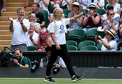Tia Carter on court ahead of performing the coin toss for the final of the Ladies' Singles on day twelve of the Wimbledon Championships at the All England Lawn Tennis and Croquet Club, Wimbledon.