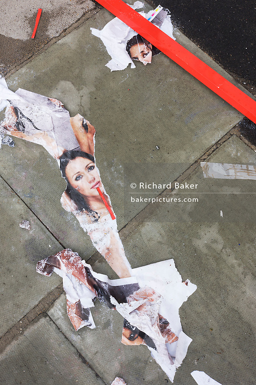 Discarded sexist ad posters lie on a London street after being removed from a refurbished shop construction site.