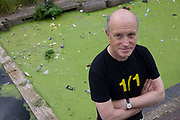 A portrait of English author/writer Ian Sinclair in his native Hackney, the location for many of his dystopian views on East London and Britain. Sinclair (1943) is a British writer and filmmaker and much of his work is rooted in London, most recently within the influences of psychogeography. His books deal with the evials of development and their fracturing of social communities – in particular, of his own home borough of Hackney and the effects from the 2012 Olympics project. His books include 'London Orbital' about the M25 motorway, 'Hackney: That Rose-red Empire' and 'Ghost Milk'. Behind him is the algae-green waters of the Regents Canal, fed by the effluent - he says - of the Olympic site.