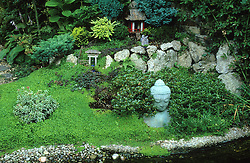 Use of stone, statues, water and Soleirolia soleirolii in a Japanese style garden