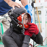 Inaba-san adjusting her mask and breathing hose before going into the ocean to work
