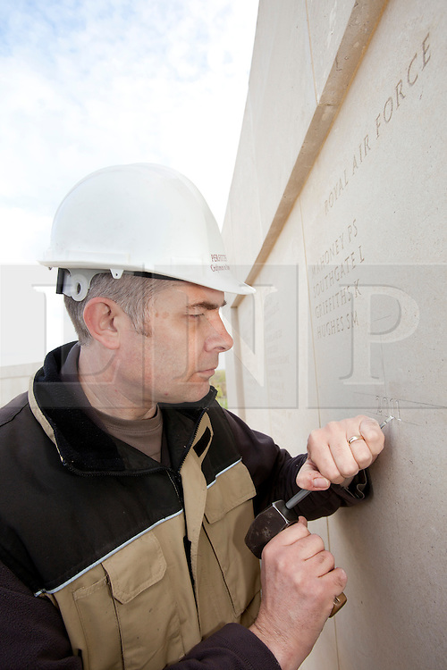 © Licensed to London News Pictures. 23/04/2012. National Memorial Arboretum, Staffordshire, UK. Engraver Nick Hindle starts the work of adding the names of Service Men and Women who lost their lives in 2011 to the Memorial Wall. Photo credit : Dave Warren/LNP.
