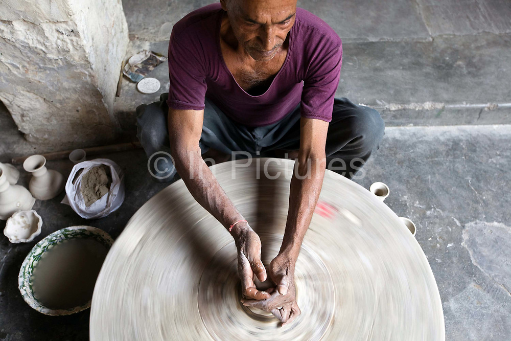 A Potter throws clay onto a wheel to make a pot at a factory in Sanganer, Jaipur, India