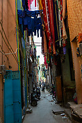 Children play and washing hangs in a narrow alleyway between two tall buildings on 18th September 2018 in Delhi, India, Asia.