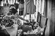 Space is at a premium backstage at the Chinese opera. The dressing room is a simple tent with makeshift preparation areas. The I-Hsin opera troupe are preparing for a performance.