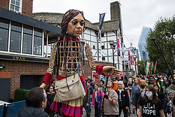 London, UK. 23rd October, 2021. Little Amal, a giant puppet of a Syrian refugee girl fleeing conflict, arrives at the Globe Theatre from St Paul's Cathedral. The 3.5-metre puppet, which is nearing the end of an 8,000km journey from the Turkish-Syrian border to Manchester in support of refugees, earlier climbed the steps of St Paul's Cathedral to present a wood carving of a ship at sea from St Paul's birthplace at Tarsus in Turkey to the dean.