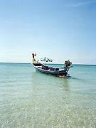 Long tail boat anchored in the clear Andaman Sea