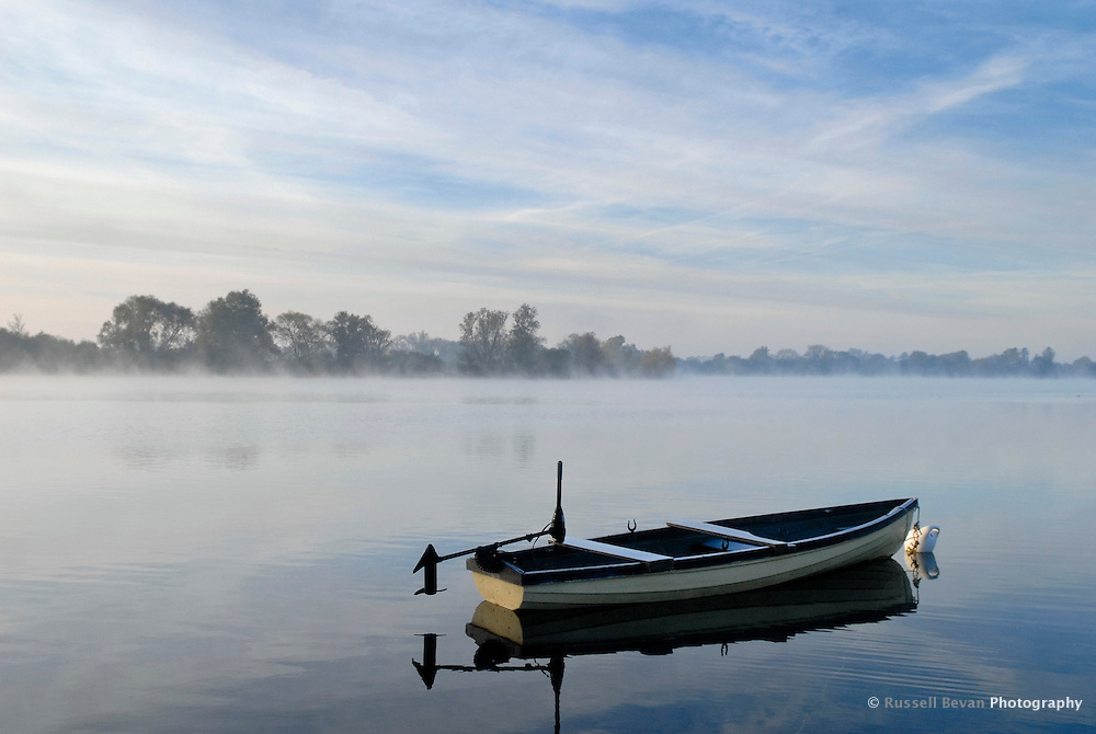 A rowing boat on a misty lake in the Cotswold Water Park