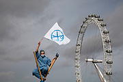 "Protester dressed as a nurse waves a flag signifying the cuts to services atop a bamboo tripod with the London Eye behind. UK Uncut shut down Westminster Bridge in a protest over NHS bill. Thousands of protesters occupied one of London's most iconic landmarks on 9 October, in a last-ditch attempt to defeat legislation that is condemned by doctors as 'undermining all that is precious about the NHS'. The anti-austerity direct action group demonstration blocked Westminster Bridge at 1pm on Sunday 9 October, days before the final vote in the House of Lords. The bill, which will see private patients treated at the expense of NHS patients, healthcare workers made redundant and reduce the priority of treating chronic and complex conditions, will be voted on by the Lords on the 12th October. The British Medical Association, the professional association of doctors in the UK, says the Bill ""presents unacceptable risks to the NHS"" and is calling for the Bill to be withdrawn."