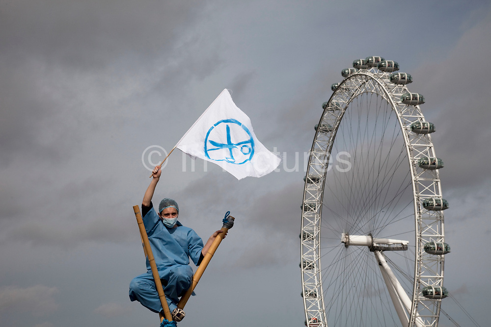 """Protester dressed as a nurse waves a flag signifying the cuts to services atop a bamboo tripod with the London Eye behind. UK Uncut shut down Westminster Bridge in a protest over NHS bill. Thousands of protesters occupied one of London's most iconic landmarks on 9 October, in a last-ditch attempt to defeat legislation that is condemned by doctors as 'undermining all that is precious about the NHS'. The anti-austerity direct action group demonstration blocked Westminster Bridge at 1pm on Sunday 9 October, days before the final vote in the House of Lords. The bill, which will see private patients treated at the expense of NHS patients, healthcare workers made redundant and reduce the priority of treating chronic and complex conditions, will be voted on by the Lords on the 12th October. The British Medical Association, the professional association of doctors in the UK, says the Bill """"presents unacceptable risks to the NHS"""" and is calling for the Bill to be withdrawn."""