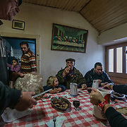 Elias Coelho (left) serves home made bread to his family and neighbors after they all spent the morning slaughtering pigs outside his home in Vilarinho Seco, one of the oldest villages in the Barroso region.