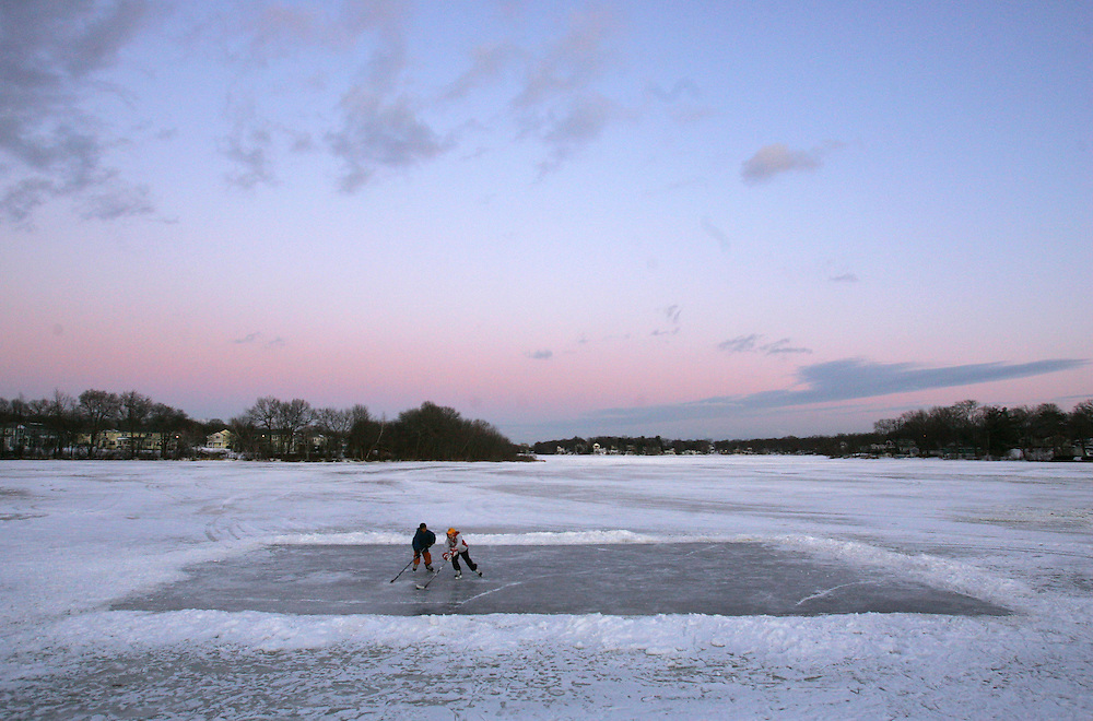Weymouth, MA 01/12/2010<br /> The sun sets over Whitmans Pond in Weymouth as Sean Walsh (left), age 12, and Billy Flynn (right), age 11, enjoy a friendly game of hockey on Tuesday afternoon.