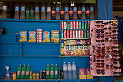 A detail of drinks and snacks on sale on blue shelving opposite the ancient Egyptian heritage site of the Colossi of Memnon on the West Bank of Luxor, Nile Valley, Egypt. The shelves are for passing tourists to buy on hot days in this part of the world and are located opposite the famous Colossi of Memnon on the road to the nearby Valley of the Kings.