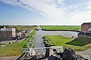 Nederland, Noordpolderzijl, 14-10-2018 In het noordelijk kustgebied van Groningen bevindt zich uitspanning het Zielhoes . Hier bevindt zich het kleinste open zeehaventje van Nederland. Een oud sluisje is in de dijk gebouwd maar wordt sinds de ophoging van de dijk niet meer gebruikt . De afwatering vanuit het Zijlriet is overgenomen door een nieuw gemaal rechts op de foto.  Veel dagjesmensen komen hier genieten van het weidse uitzicht . Kwelders. Vroeger werden de kwelderwerken gebruikt om de kwelderaangroei te versnellen zodat ze na verloop van tijd konden worden ingepolderd. Noordpolderzijl is onderdeel van de gemeente Eemsmond . Foto: ANP/ Hollandse Hoogte/ Flip Franssen