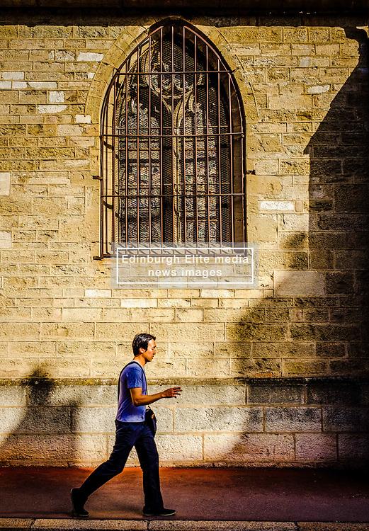 A man walks past the Notre Dame church in Beaune, Burgundy, France<br /> <br /> (c) Andrew Wilson | Edinburgh Elite media