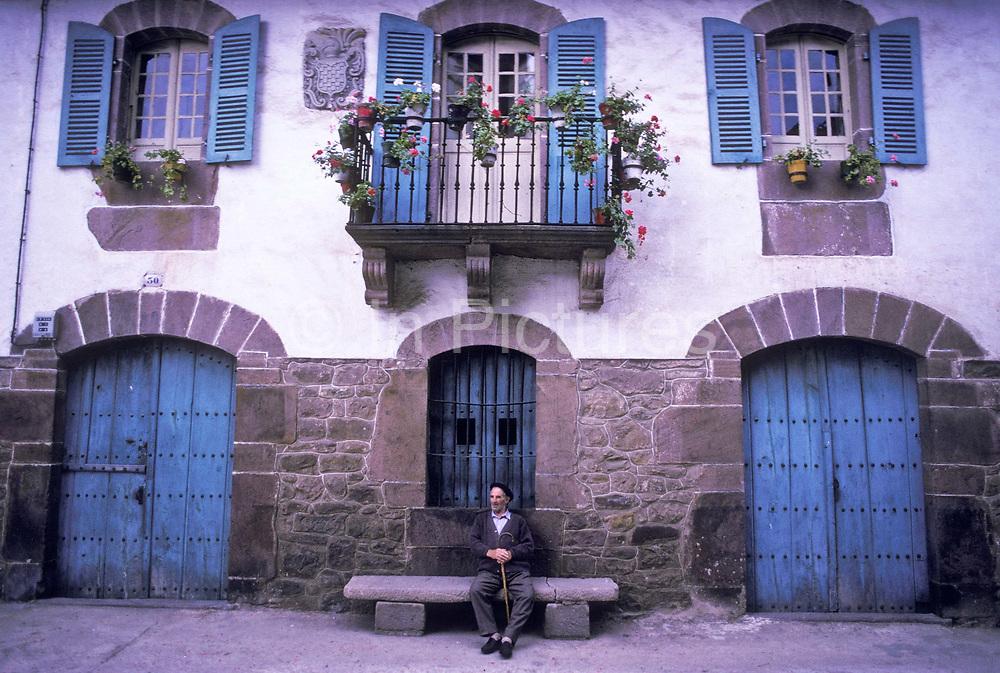 A villager sits on bench infront of house, Errazu village, Baztan, Basque country, Spain.