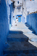 Boy walking up the steps of an alley in the medina of Chefchaouen, Morocco.