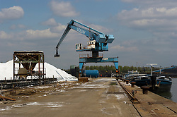 A crane is used to move mounds of salt used for producing chlorine, at the Solvay SA chemical plant in Antwerp, Belgium, on Thursday, April 22, 2010.  Solvay SA is the world's largest supplier of Soda Ash or Sodium Carbonate and is also a major producer of caustic soda, hydrogen peroxide, chlorine and fluorinated products. (Photo © Jock Fistick)