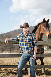 sexy cowboy with horse on a ranch