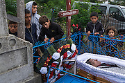 Deceased Roma man in open coffin during his funeral in the village of Valea Seaca in Bacau County, Romania.