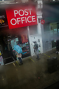 """People queue at a Post Office in Green Lanes,  London, as heavy rain batters the capital, in London, Friday, Oct. 2, 2020. Britain is facing gales and heavy downpours as the storm """"Alex"""" is reaching its coasts. (VXP Photo/ Sabrina Merolla)."""